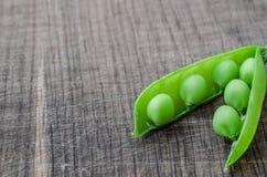Guisantes orgánicos verdes en fondo de madera Foto de archivo libre de regalías