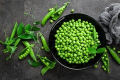 Guisantes verdes con las vainas y las hojas Fotos de archivo libres de regalías