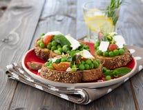 Guisantes verdes con los tomates, el queso feta y la menta de cereza en tostada foto de archivo
