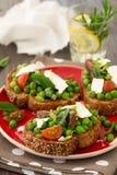 Guisantes verdes con los tomates, el queso feta y la menta de cereza en tostada fotografía de archivo libre de regalías