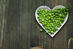 Guisantes verdes en cuenco en fondo de madera oscuro Fotografía de archivo libre de regalías