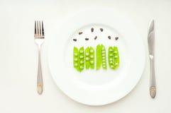 Guisantes verdes en habas con las nueces de cedro en la placa blanca Foto de archivo libre de regalías