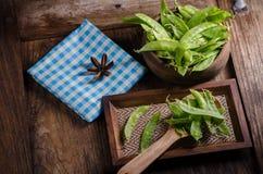 Guisantes verdes en la tabla de madera Fotografía de archivo