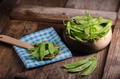 Guisantes verdes en la tabla de madera Fotografía de archivo libre de regalías
