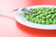 Guisantes verdes en placa Imagen de archivo libre de regalías
