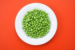 Guisantes verdes en placa Fotos de archivo