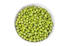 Guisantes verdes en un cuenco blanco en un fondo blanco Aislado Visión superior imagenes de archivo