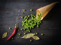 Guisantes verdes en un documento y pimientas de chile sobre un fondo de madera oscuro Imagen de archivo
