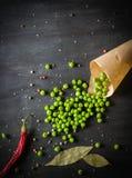 Guisantes verdes en un documento y pimientas de chile sobre un fondo de madera oscuro Foto de archivo