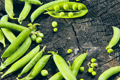 Guisantes verdes en un tocón en un fondo de madera Foto de archivo