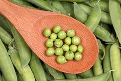 Guisantes verdes en una cuchara de madera Fotos de archivo