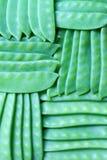 Guisantes verdes jovenes en fondo de las vainas Imagenes de archivo