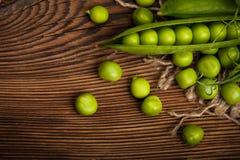 Guisantes verdes orgánicos frescos en un fondo de madera Estilo rústico Fotos de archivo