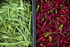 Guisantes verdes y pimientas de chiles en cajas foto de archivo