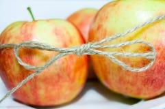A guita amarra acima o close up de três maçãs Foto de Stock
