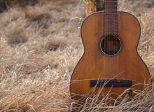 Guitar. Old acoustic guitar with scratches in the dry grass with back sun,autumn (fall) nature environment - backlight Stock Image