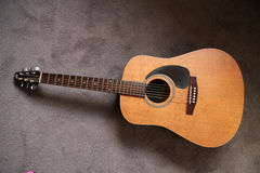 Guitar. A wooden guitar with a brown background Royalty Free Stock Photography