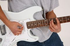 Guitar 2. Torso of a guy playng an electric guitar against a high key backgrund Royalty Free Stock Photo