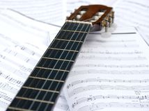 Guitar. Acoustic guitar head and neck over sheet music Royalty Free Stock Photos