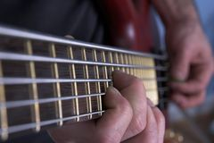 Guitar. Closeup of hands playing bass guitar Royalty Free Stock Image