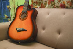 Guitar. Called over the sofa set with flower Stock Photos