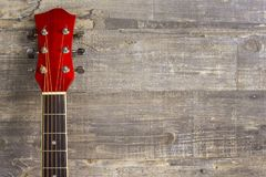 Guitar acoustic red, neck lying on a vintage background of wood on the background of old grunge boards. Place for text stock photo