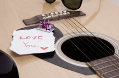 Guitar acoustic. Vintage style,Guitar acoustic and short note (i love you) on old wood background Stock Images