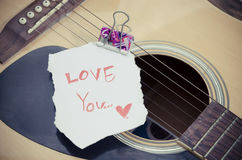 Guitar acoustic. Vintage style,Guitar acoustic and short note (i love you) on old wood background Royalty Free Stock Images