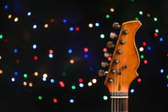 Guitar against blurred lights. Christmas music. Concept royalty free stock images
