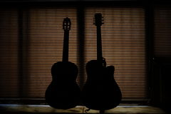 Guitar Amazing Gesture. Amazing black shaded acoustic guitars with orange background Royalty Free Stock Photo