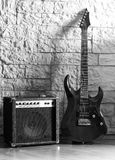 Guitar and amplifier on a stone background. Guitar and amplifier, black and white photo Stock Images