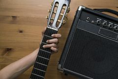 Guitar amplifier and woman hand holding a guitar on wood table. Top view Royalty Free Stock Photo