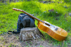 The guitar and backpack on a green glade Stock Photos