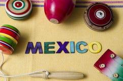 Guitar, balero, yoyos and maracas, traditional mexican toys. On yellow tablecloth