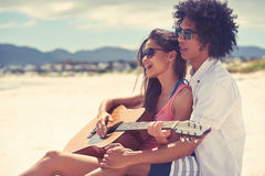 Guitar beach couple. Cute hispanic couple playing guitar serenading on beach in love and embrace Stock Image