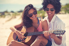 Guitar beach couple. Cute hispanic couple playing guitar serenading on beach in love and embrace Royalty Free Stock Photos