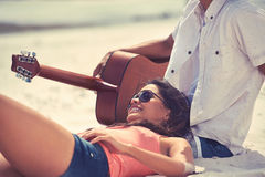Guitar beach couple. Cute hispanic couple playing guitar serenading on beach in love and embrace Stock Photo