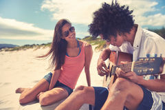 Guitar beach couple. Cute hispanic couple playing guitar serenading on beach in love and embrace Stock Photos