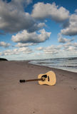 Guitar at the  beach. Dark clouds behind a guitar at the beach Royalty Free Stock Images