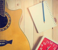 Guitar with blank book for Music Writing time. Song writing and Music equipments on wooden background Stock Image