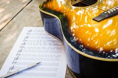 Guitar and blank notebook. Stock Images