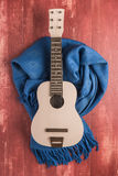 Guitar and blanket on rustic wooden background texture Royalty Free Stock Photos