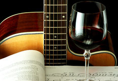 Guitar, book and wineglass. Acoustic guitar, book with notes and wineglass with red wine on the dark background Royalty Free Stock Images