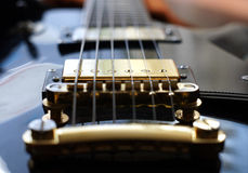 Guitar bridge. Close-up of golden guitar bridge and strings Stock Photography