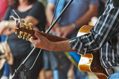Guitar Busker. A musician busks with his acoustic guitar in the street as the crowd watches on Royalty Free Stock Photo