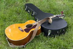 Guitar and case on ground Royalty Free Stock Images