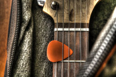Guitar in the case. Guitar and pick in the case in HDR Stock Photo