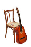 Guitar by a chair Royalty Free Stock Photos
