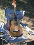 Guitar on a chair. An acoustic guitar on w folding chairs in the sun Stock Photo