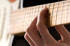 Guitar chord. Hand playing guitar chord with shallow depth of field Royalty Free Stock Images